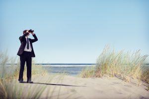 Hombre con traje en la playa buscando la ola adecuada