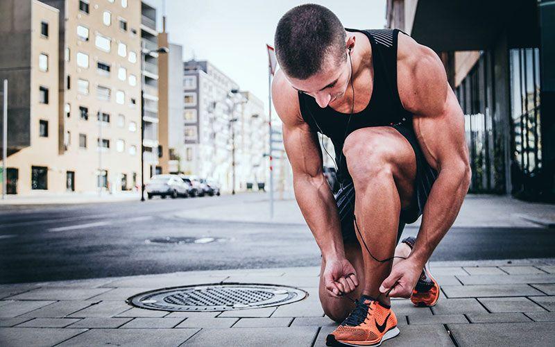 joven deportista atándose las zapatillas en running